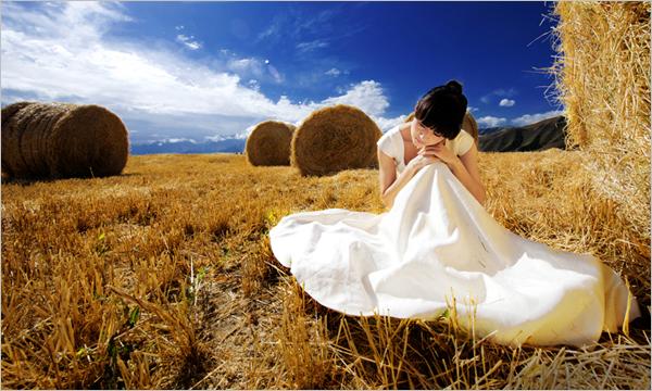 高山麦场 光圈:f/,快门:1/s   这一处场景是连绵起伏的天山麦场,高山麦田最具代表性的景物是圆柱形的高大麦垛,远处的雪山、松林,近处的草场和麦地遥相呼应。在这样的场景中拍摄,表现的重点在于辽阔的麦地、巨大的麦垛和丰富饱和的色彩。人物身处其中,能够表现出一种成熟季节的遐想和感怀。适宜在天气晴好时拍摄,蓝天白云加上金黄的麦田,色彩层次丰富。因为场景阔大,主要利用自然光线,尤以侧光为主进行拍摄。在这样的光线条件下,色彩表现充分,质感突出,人物和麦垛的立体感更强。