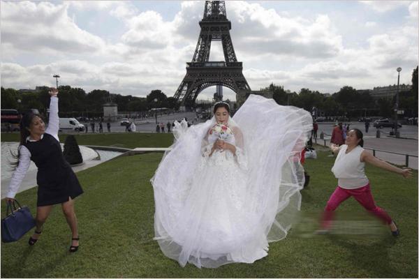 """2015年8月,法国巴黎,身穿西方婚礼服饰的一对中国情侣在巴黎圣母院前紧握双手、深情对视,两名摄影师在旁边捕捉镜头。在这对打算明年在国内举办婚礼的年轻夫妇旁边几米处,两对中国夫妇也在拍摄婚纱照,另外还有一对夫妇在等待。据路透社报道,随着中国年轻人越来越富裕,婚前到国外拍摄婚纱照蔚然成风。    拍婚纱照的中国夫妇在埃菲尔铁塔、巴黎圣母院和塞纳河的桥上随处可见,也成了一道风景。   """"我们将在婚礼上展示这些照片,""""一位手捧白花的25岁新娘说道。很多游客为这对夫妇拍手喝彩。&ldq"""