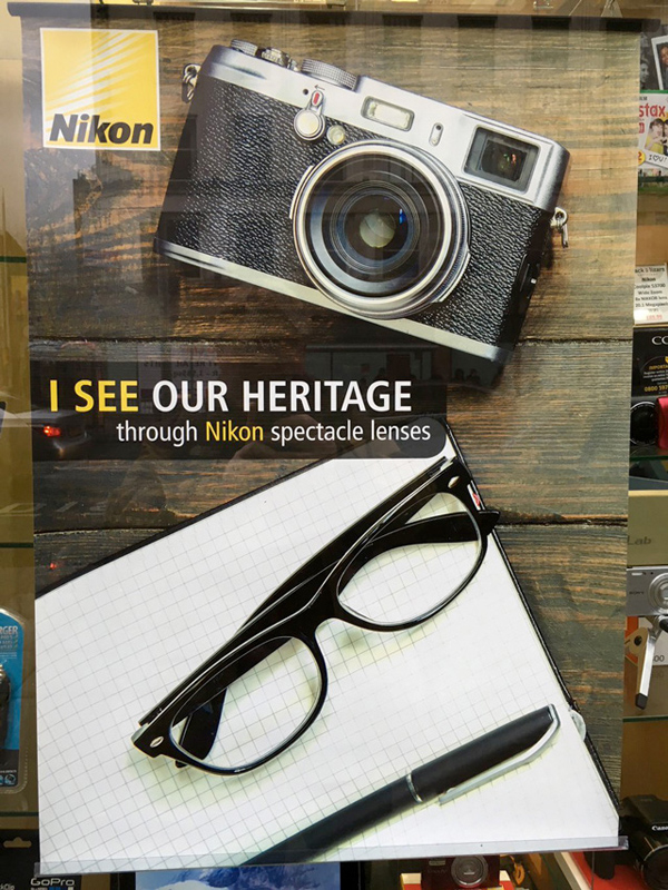 """尽管这几年摄影圈兴起的复古风潮主要要归功于富士,但是在自己海报上放上其他品牌的相机,并用来宣传自己品牌的""""Heritage""""是不是显得有些好笑呢?作为数码影像大厂的尼康最近就犯下了这么一个""""美丽错误""""。   近日设计师David McDonald在一家位于北爱尔兰的店铺中发现了一幅尼康眼镜的宣传海报,海报的主题似乎意在表现出尼康眼镜(镜片)与自家镜头技术之间的传承关系,然而海报的上方却出现了一部外观类似富士X100的相机,按理说尼康完全可以放上自家的DF"""