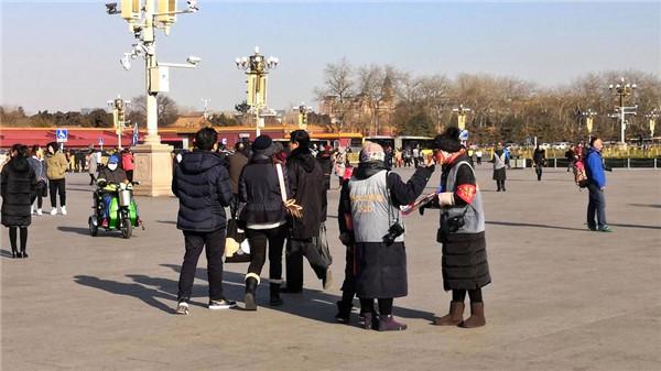 天安门广场上,寒风中给游客拍照的摄影师生意冷淡