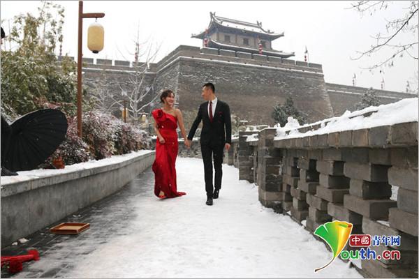 """美丽""""冻人"""" 西安多对新人大雪纷飞中拍婚纱照"""